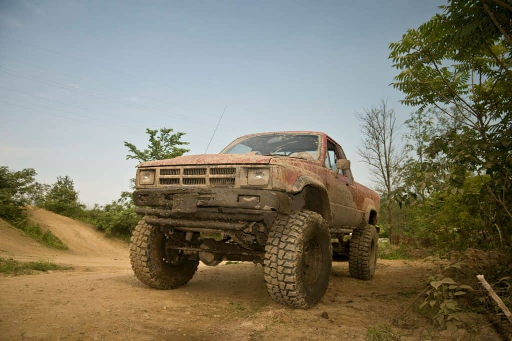 A 1984 Toyota pickup truck covered with mud on dirt trails