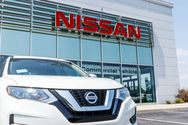 A Nissan Altima parked outside a Nissan dealership, Does The Nissan Altima Have Bluetooth? [And What You Need To Know About It]