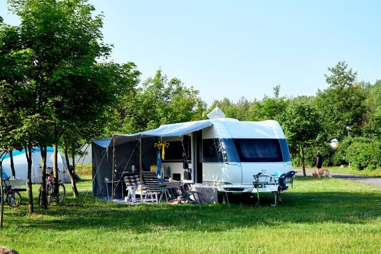 A camper trailer set up near a scenic view of a lake with chairs and awning set up outside, What Toy Haulers Have The Largest Garages?
