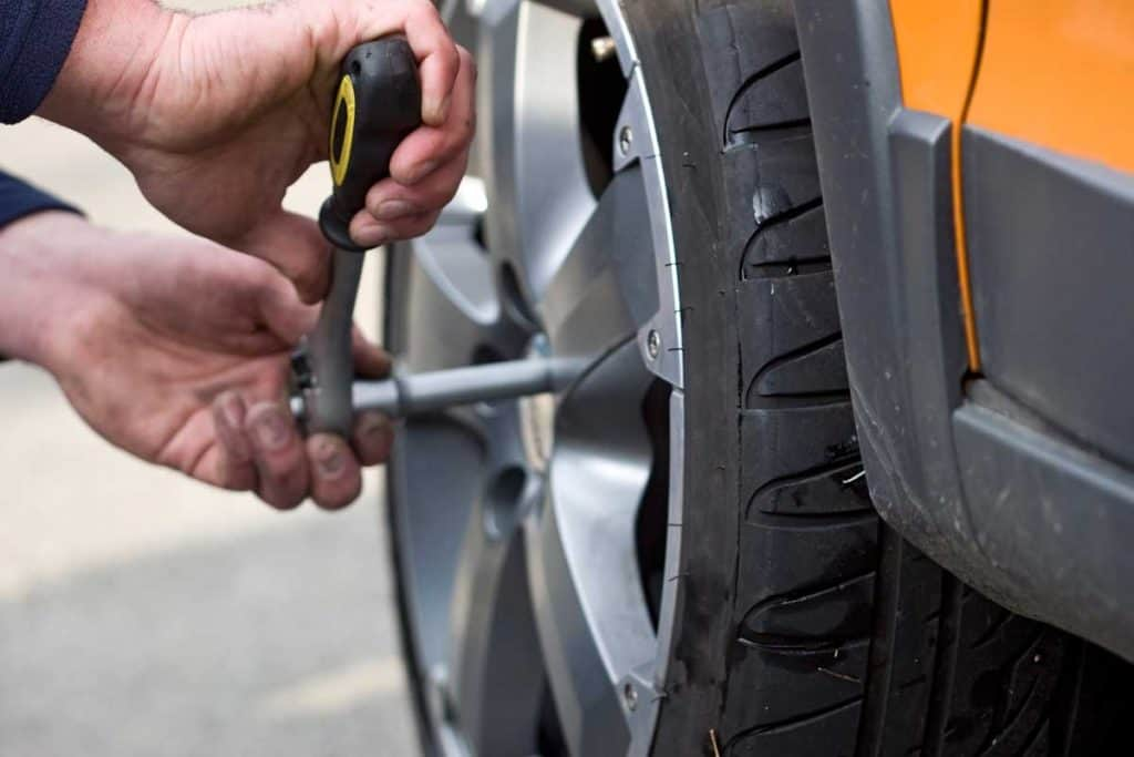 A man changing wheel of a car, Should You Rotate Tires On AWD And 4WD Vehicles?
