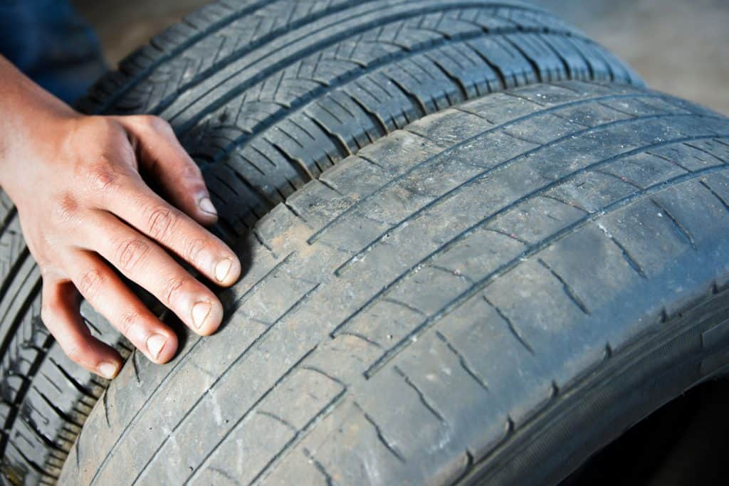 A man comparing a worn out tire and a brand new one