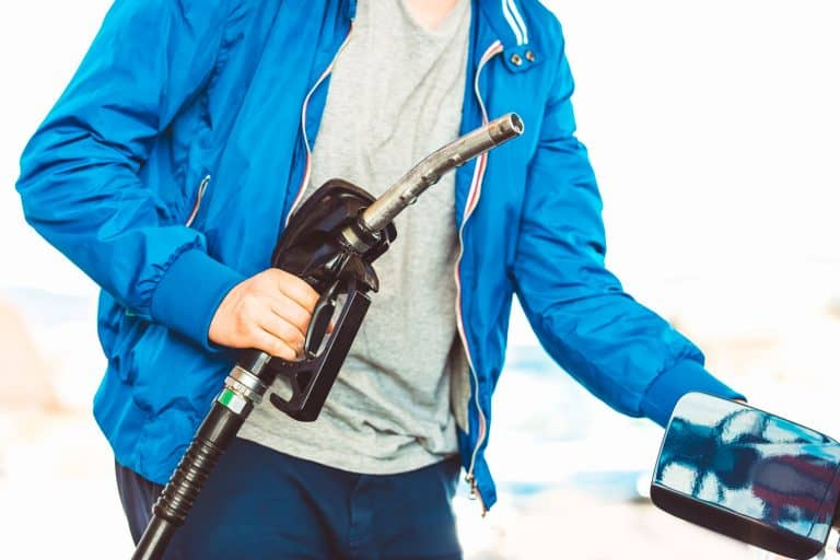 A man holding a black fuel pump while opening the fuel cover of his car, Are Diesel Nozzles Bigger Than Gas?