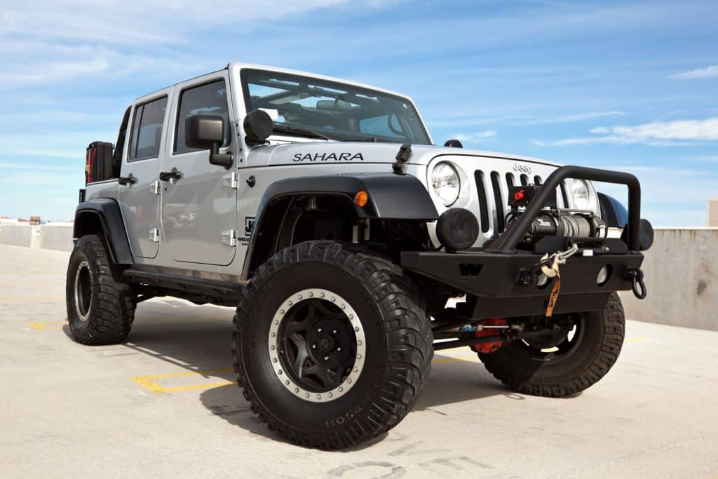 A parked silver 2008 Jeep Wrangler, this particular Jeep has a custom shock kit and winch and is known as the Sahara edition