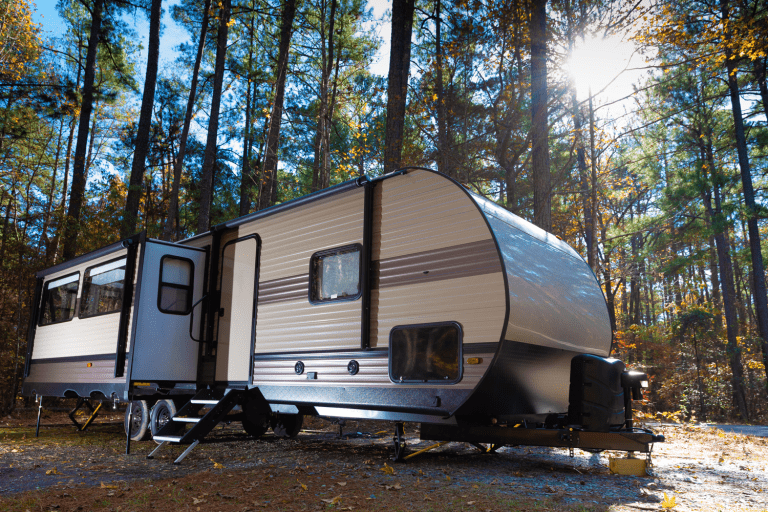 A travel trailer set up in a forestry area, How To Turn A Toy Hauler Ramp Into A Patio [Inc. A Conversion Kit]