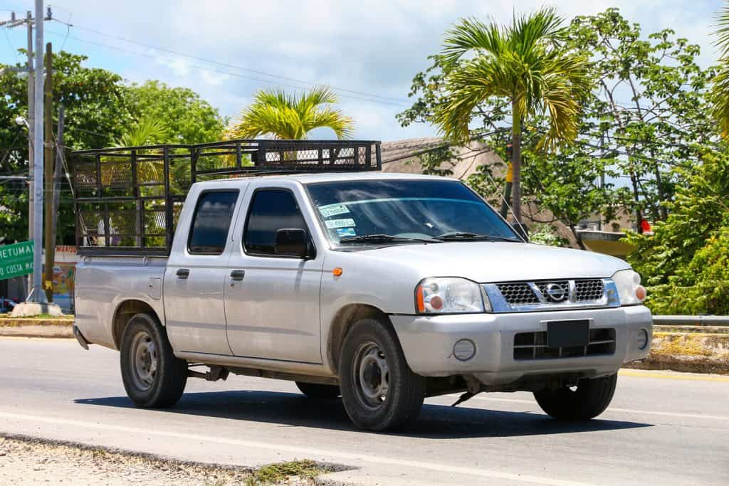 A white Nissan Frontier D22 with cages on the back