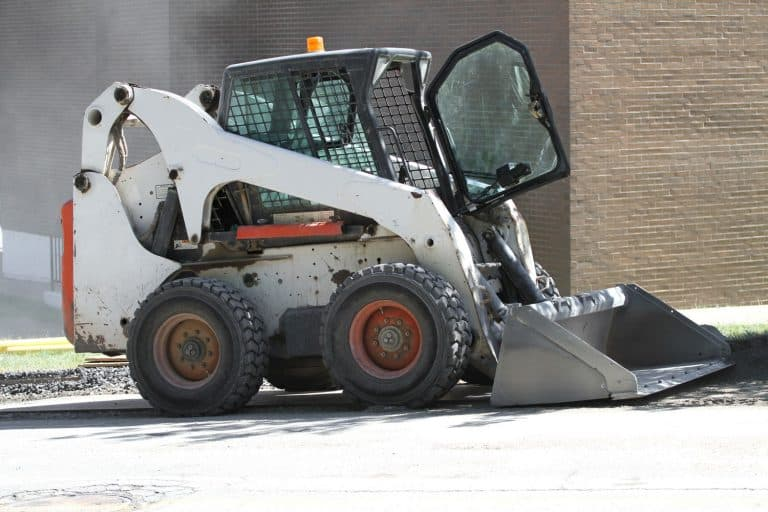 A white Skid loader with the operators door left open, What Year Is My Bobcat? [By Serial Number]