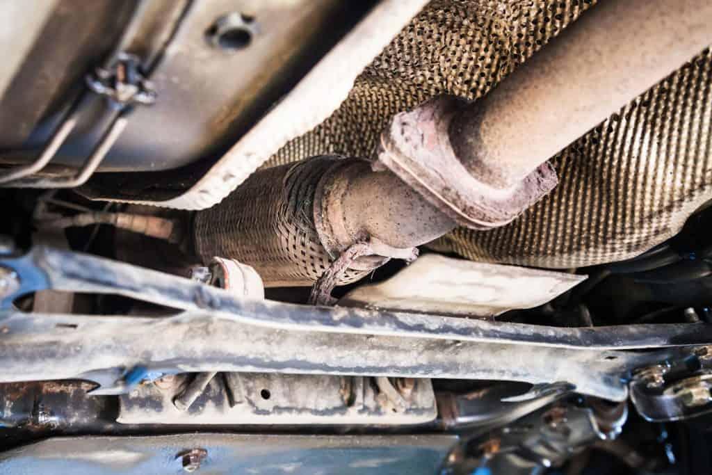 Bottom view of broken corrugation muffler on car