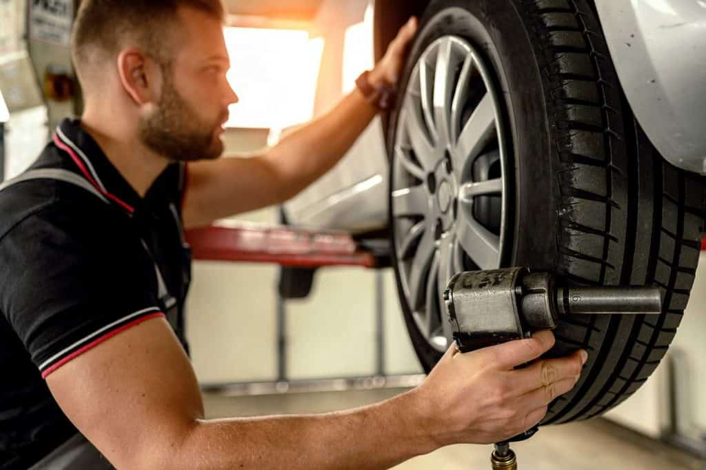 Car mechanic changing tire at car service