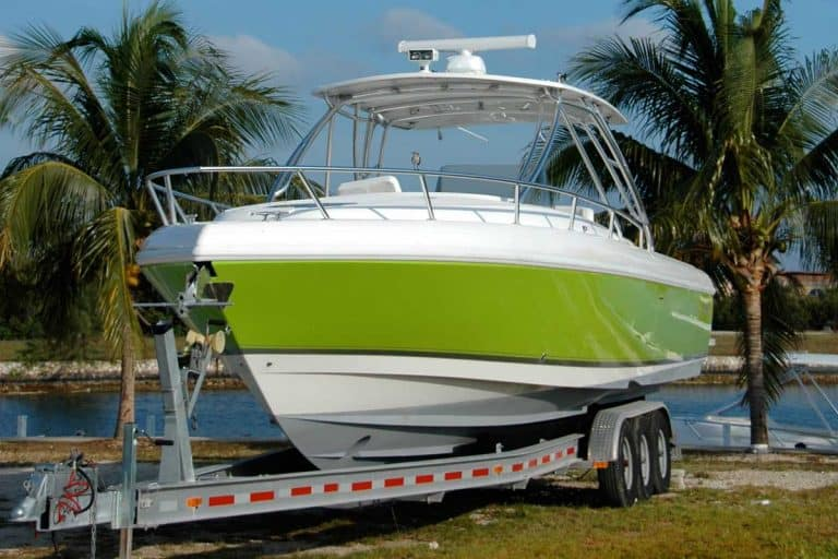 Lime green power boat on a trailer with palm trees and water behind, Can You Fit A Boat In A Toy Hauler?