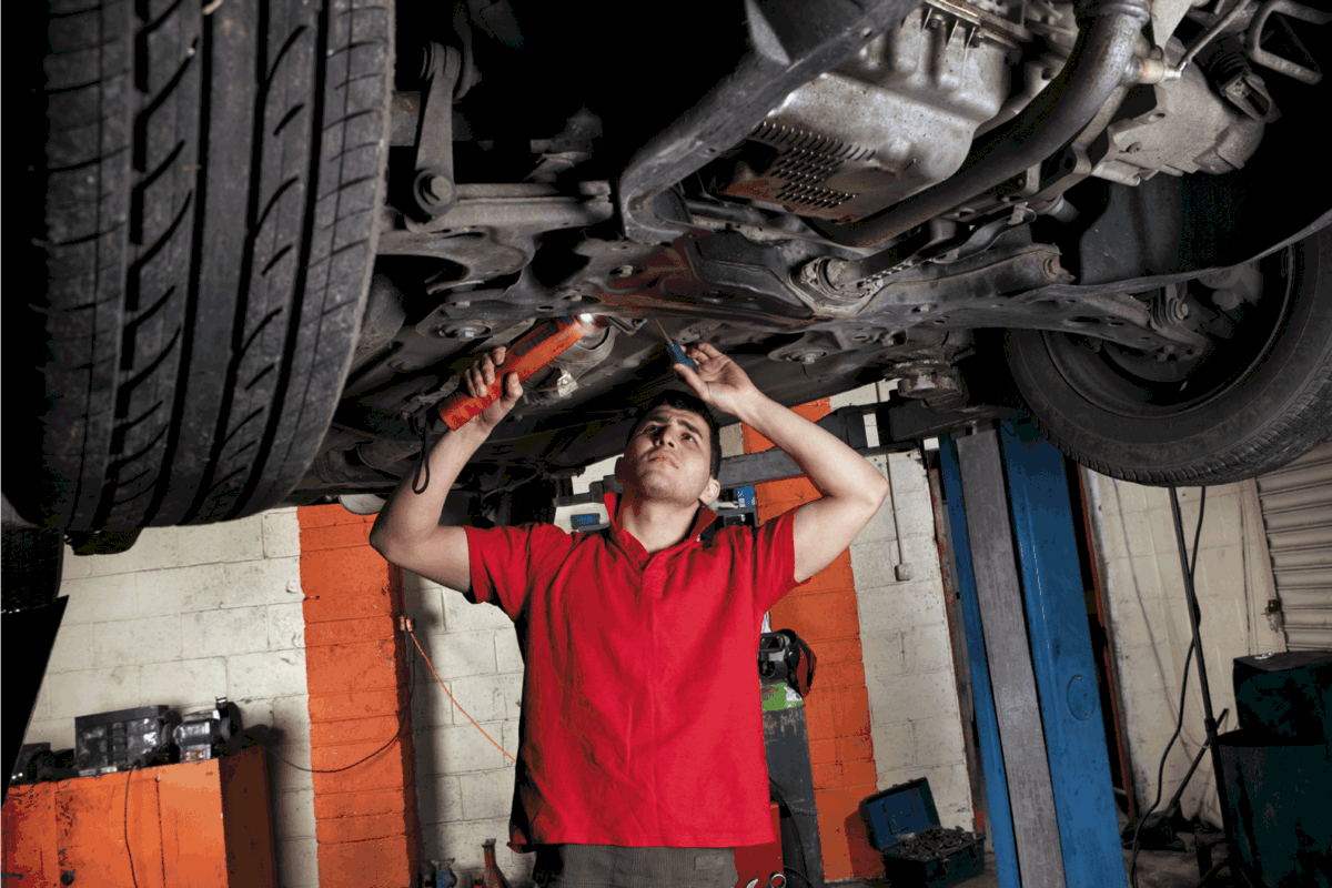 Mechanic inspecting underneath the car with a torch and a screwdriver. Can An Exhaust Leak Cause Misfire