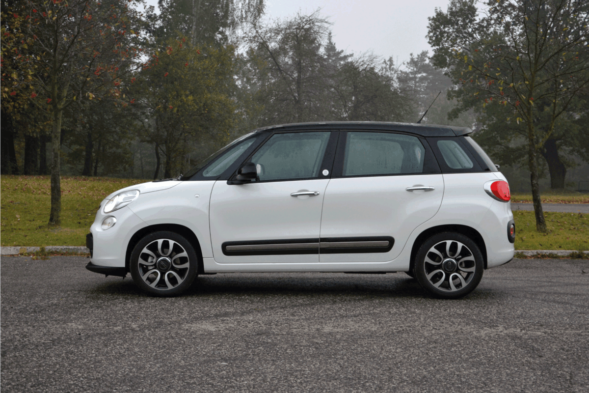 Minivan Fiat 500L parked on a street with light fog and trees. Does A Fiat 500L Have A Spare Tire