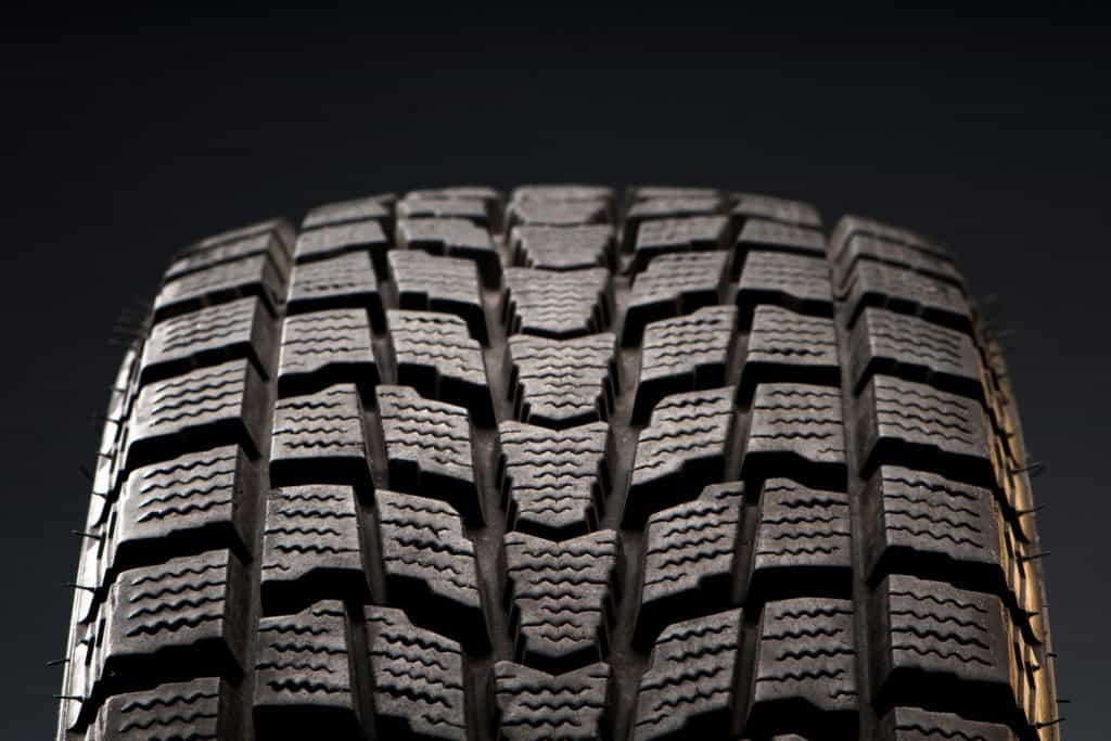 New car tire with unscathed tire treads on a dark background