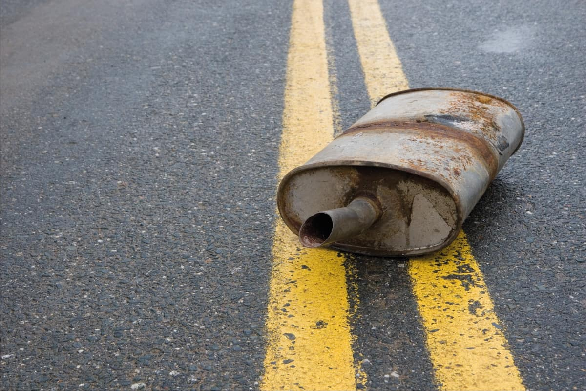 Old rusted muffler laying in the center of the road