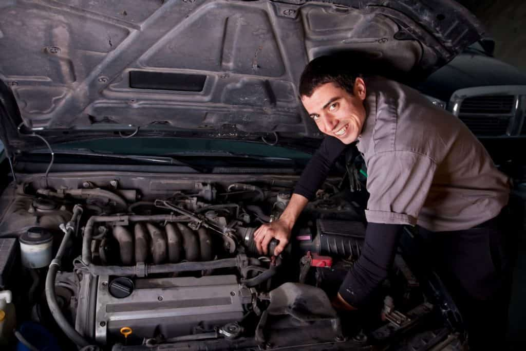 Smiling male auto repair mechanic works on an engine