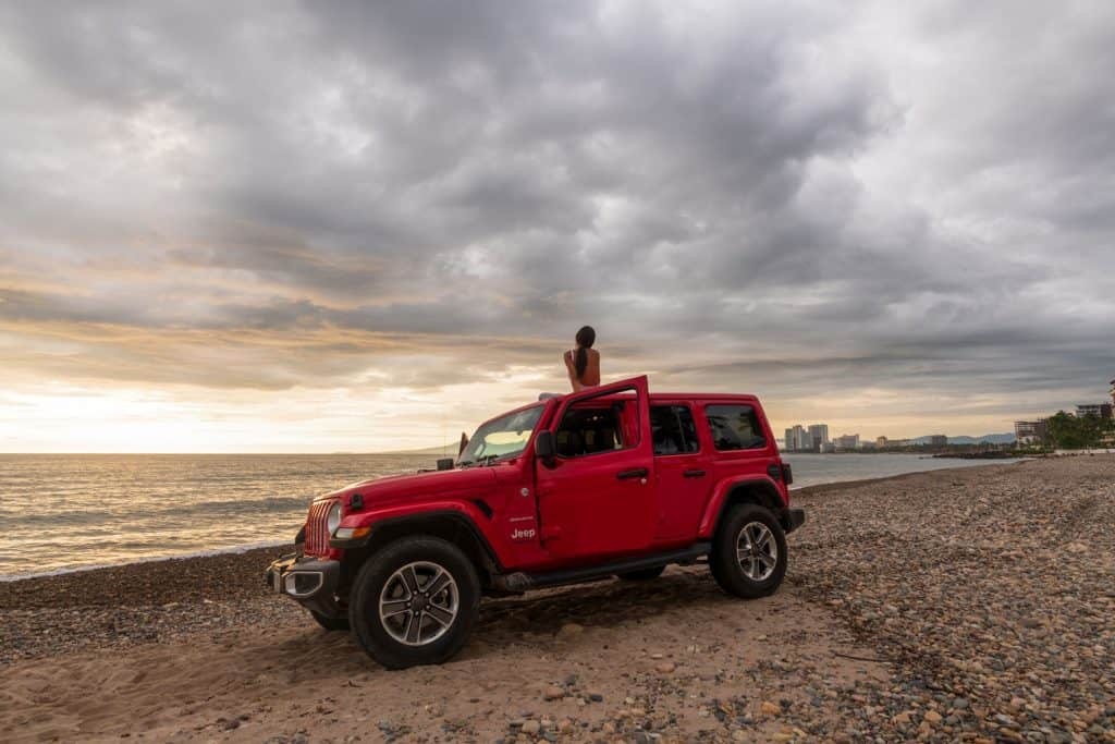 The 2019 Jeep Wrangler Unlimited Sahara off-road with the ocean and cityscape in the background