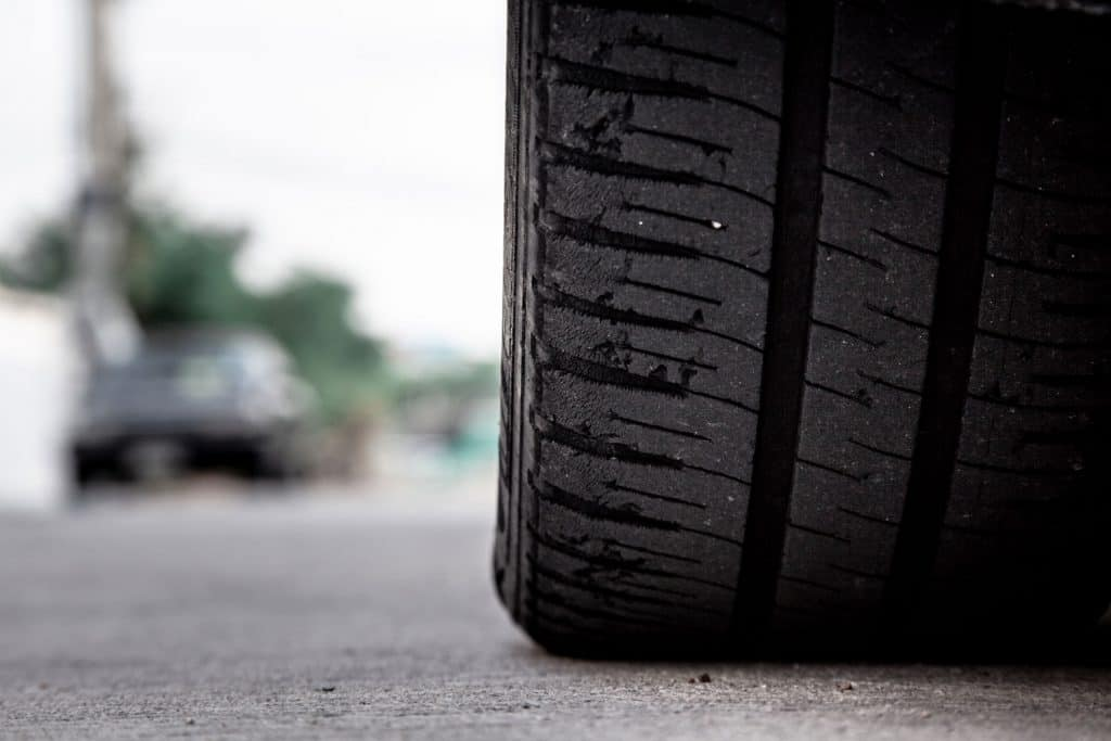 Tire wear concept. Danger of using old car bald tire with very little tread remaining