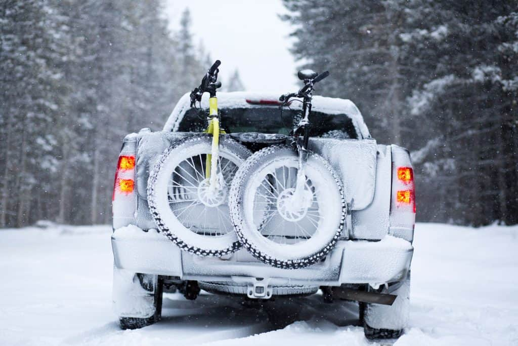 Two fat bikes are transported on the tailgate of a truck during a snowstorm