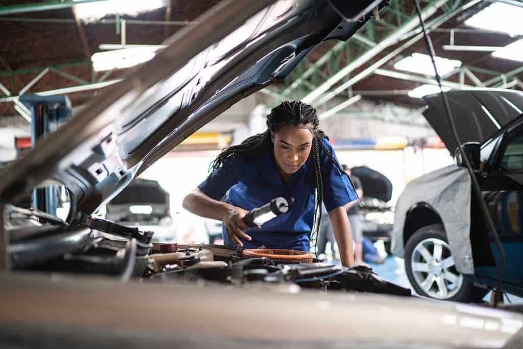 Woman repairing a car in auto repair shop