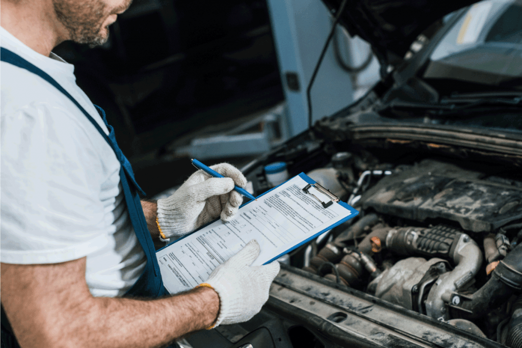auto mechanic in gloves and cap looking at car engine. Can An Exhaust Leak Cause Misfire